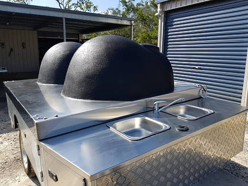 Twin wood fired ovens mounted on a sturdy trailer