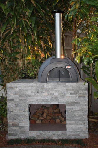An Alfresco wood fired oven built on a grey brick base
