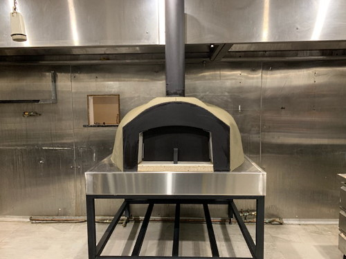 An oven from Sydney Wood Fire Ovens mounted on a metal frame