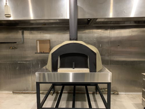 A small commercial grade wood fired oven mounted on a metal frame
