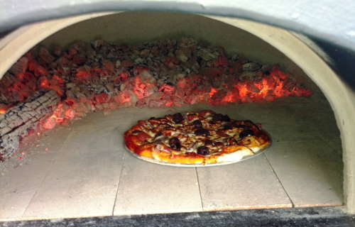 delicious looking pizza cooking in a hot wood fired oven