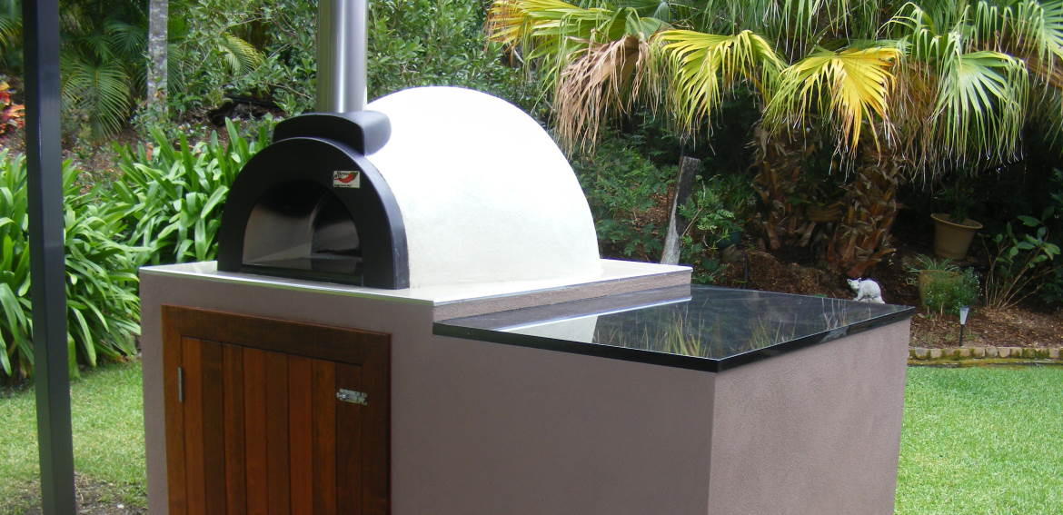 a wood fired pizza oven set in a lush tropical garden